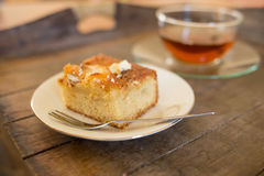 Piece of cake with a cup of tea on a serving plate Royalty Free Stock Photography