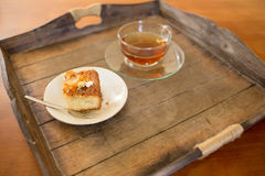 Piece of cake with a cup of tea on a serving plate Stock Photo