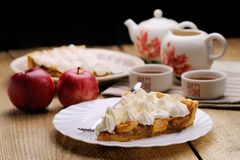 Piece of cake decorated with whipped cream with teaware and appl. Es side view on wooden background Stock Image