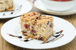 Piece of cake with dried cranberries and nuts decorated with cho Stock Photo
