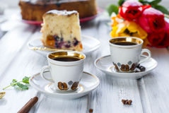 Piece of cake with fruit and two cups of coffee Stock Images