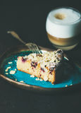 Piece of cake and glass of latte over dark background Stock Images
