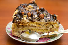 Piece of cake with hazelnuts and chocolate in a saucer. With a teaspoon - background Royalty Free Stock Photo