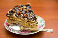 Piece of cake with hazelnuts and chocolate in a saucer. With a teaspoon - background Stock Photography
