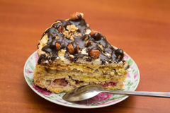 Piece of cake with hazelnuts and chocolate in a saucer. With a teaspoon - background Royalty Free Stock Image