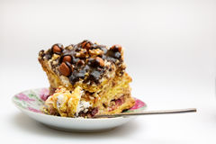 Piece of cake with hazelnuts and chocolate in a saucer. With a teaspoon - background Stock Images