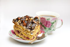 Piece of cake with hazelnuts, teaspoon and cup. Piece of cake with hazelnuts and chocolate in a saucer, with a teaspoon and a cup of coffee, tea - background Stock Image