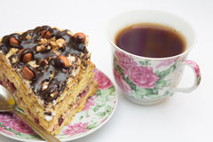 Piece of cake with hazelnuts, teaspoon and cup. Piece of cake with hazelnuts and chocolate in a saucer, with a teaspoon and a cup of coffee, tea - background Royalty Free Stock Images