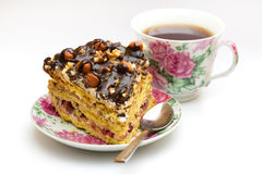 Piece of cake with hazelnuts, teaspoon and cup. Piece of cake with hazelnuts and chocolate in a saucer, with a teaspoon and a cup of coffee, tea - background Royalty Free Stock Photography