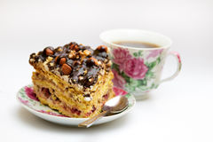 Piece of cake with hazelnuts, teaspoon and cup. Piece of cake with hazelnuts and chocolate in a saucer, with a teaspoon and a cup of coffee, tea - background Stock Photos