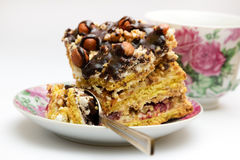 Piece of cake with hazelnuts, teaspoon and cup. Piece of cake with hazelnuts and chocolate in a saucer, with a teaspoon and a cup of coffee, tea - background Royalty Free Stock Photo