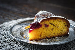 Piece of cake with icing sugar and jam on the lace napkin close - up Royalty Free Stock Photo