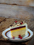 Piece of cake `Napoleon`: crispy cakes with cream, orange cream, cranberry jelly, cheese mousse. Side view. Stock Image