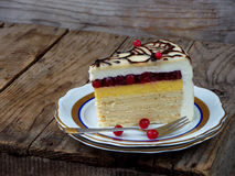 Piece of cake `Napoleon`: crispy cakes with cream, orange cream, cranberry jelly, cheese mousse. Side view. Royalty Free Stock Image