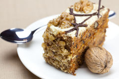 Piece of cake with nuts and spoon Royalty Free Stock Image