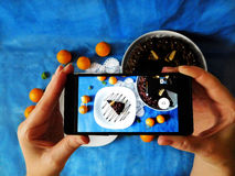 A piece of cake photographed with a smartphone. A piece of chocolate cake on a plate seeing trough smartphone camera stock photo