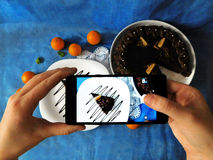 A piece of cake photographed with a smartphone. A piece of chocolate cake on a plate seeing trough smartphone camera royalty free stock images