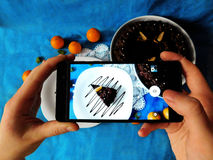 A piece of cake photographed with a smartphone. A piece of chocolate cake on a plate seeing trough smartphone camera stock image