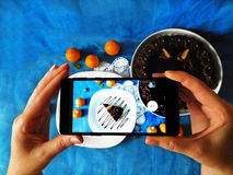 A piece of cake photographed with a smartphone. A piece of chocolate cake on a plate seeing trough smartphone camera royalty free stock image