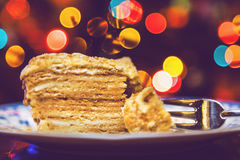 Piece of cake on plate lying on background Christmas lights Stock Photo