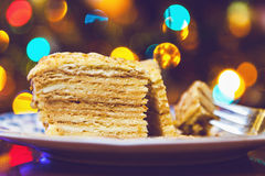 Piece of cake on plate lying on background Christmas lights Royalty Free Stock Photography