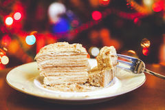 Piece of cake on plate lying on background Christmas lights Royalty Free Stock Images