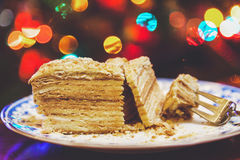Piece of cake on plate lying on background Christmas lights Royalty Free Stock Image