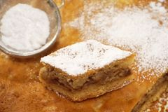 Piece of cake with powdered sugar on baked biscuit stock photo