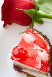 A piece of cake and a red rose Stock Photos