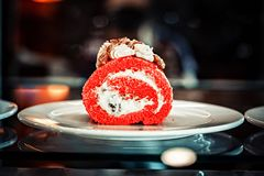 A piece of cake roll in unusually red color. in the interior on white dishes stock images