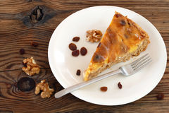 Piece of cake, some raisins, walnuts and cake fork on an oldwood Stock Photos