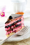 Piece of cake with souffle and blackcurrant jelly on a white pla Stock Images