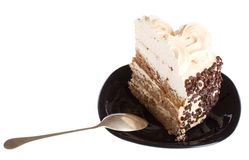 Piece of cake and spoon on black plate Royalty Free Stock Photos