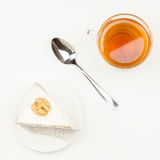 Piece of cake, spoon, tea  on a white surface. Piece of cake, spoon, tea lying on a white surface Royalty Free Stock Image