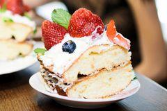 A piece of cake with strawberries in cream stock image