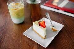 A piece of cake with strawberry on top. Cold coffee. royalty free stock images