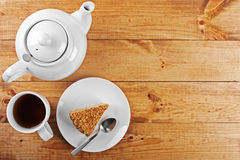 Piece of cake and tea pot on wooden table Royalty Free Stock Photo
