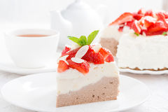 Piece of cake with whipped cream, fresh strawberries and tea Stock Image