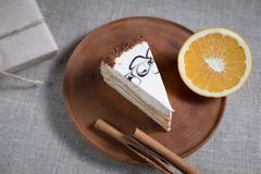 Piece of cake with white chocolate and orange and cinnamon sticks lying on a wooden plate royalty free stock image