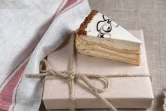 Piece of cake with white chocolate and the ornament rests on a gift box. With cleaning cloth Royalty Free Stock Images