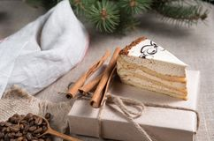 Piece of cake with white chocolate and the ornament rests on a gift box. With cleaning cloth Stock Photos