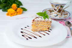 A piece of cake, white cup of tea and strawberries. Piece of cake with flowers on a plate and tea Stock Photos