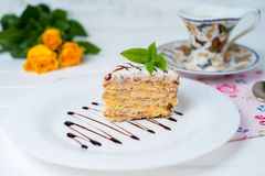 A piece of cake, white cup of tea and strawberries. Piece of cake with flowers on a plate and tea Stock Image