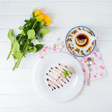 A piece of cake, white cup of tea and strawberries. Piece of cake with flowers on a plate and tea Royalty Free Stock Photo