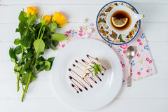 A piece of cake, white cup of tea and strawberries. Piece of cake with flowers on a plate and tea Stock Photo