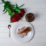 A piece of cake, white cup of tea and strawberries. Selective focus. Piece of cake with flowers on a plate and tea. Selective focus Royalty Free Stock Images
