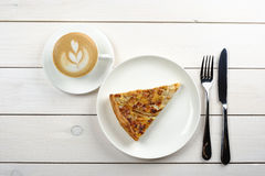 A piece of cake on a white plate with a Cup of cappuccino and Cutlery on a white wooden table. Top view. Tasty piece of cake on a white plate with a Cup of Royalty Free Stock Image