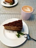 A piece of cake on a white plate on a table in a cafe near a cup of coffee cappuccino royalty free stock photo