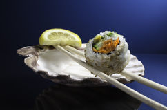Piece of California Roll Sushi. A piece of California Roll sushi on a pair of chopsticks with sea shell background Royalty Free Stock Image
