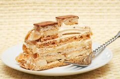 Piece of caramel meringue cake. Slice of caramel meringue cake with cream and almonds, shot on a light wooden background Stock Photography